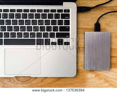 Top view of external or portable hard drive (HDD) connected to laptop computer for transfer or backup data on wooden texture office desktop