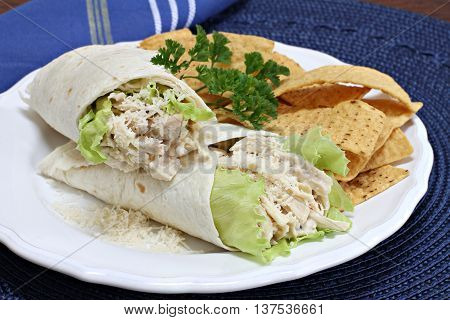 Stacked chicken caesar salad sandwich wraps with a side of tortilla chips.