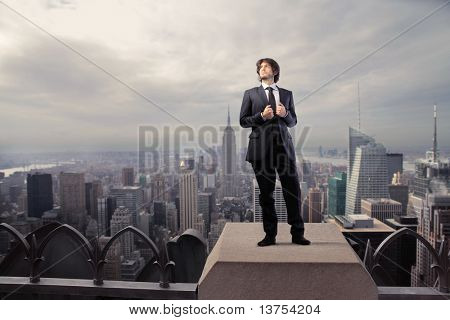 Businessman standing on the rooftop of a skyscraper
