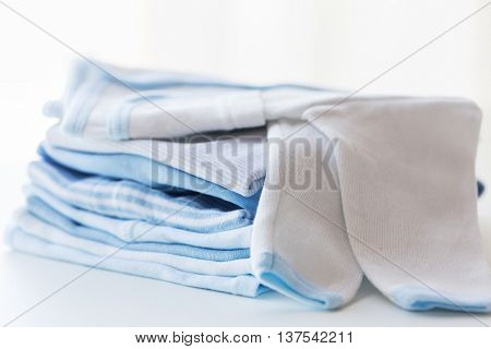 clothing, babyhood, motherhood and object concept - close up of white baby cardigan with pile of folded clothes for newborn boy
