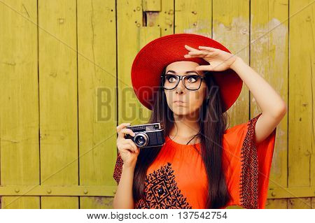 Undecided Girl with Retro Photo Camera and Red Sun Hat