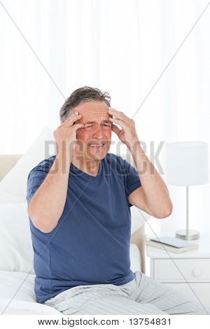 Man having a headache on his bed poster