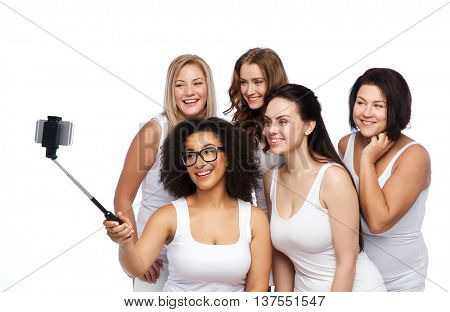 technology, friendship, body positive and people concept - group of happy women in white underwear taking picture with smartphoone on selfie stick