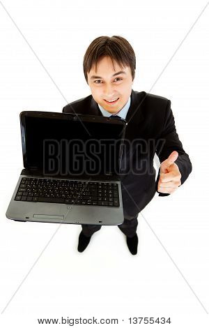 Smiling businessman holding laptops blank screen and showing thumbs up gesture isolated on white