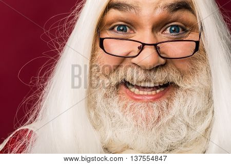 old bearded professor man wizard in glasses with blue lenses in eyes with long gray beard and white hair has emotional smiling happy face on purple background portrait