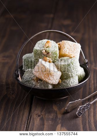 Heap of turkish delights in vase on wooden background