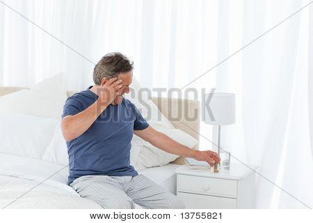 Man having a headache on his bed