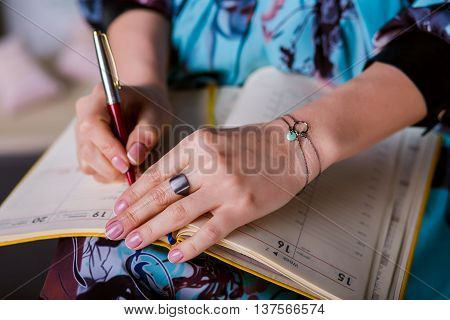 take notes idea. Woman wrote a note in diary. Closeup beautiful female hand writing notes.