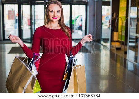 Portrait of beautiful happy welldressed woman with shopping bags. Shopping center. Successful Day sales