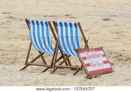 Stripey Deckchairs on hire on sandy beach