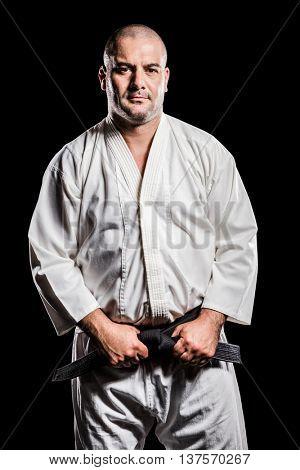 Portrait of fighter tightening karate belt on black background