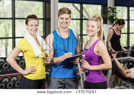Trainer man talking with sportswomen at gym