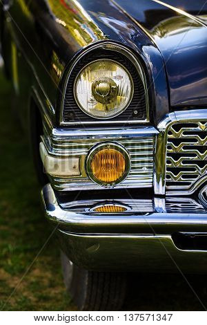 MINSK BELARUS - MAY 07 2016: Chaika GAZ-13 - Soviet car. Close-up of the headlights and the front part of an old black vintage retro auto Chaika GAZ-13. Selective focus on the car's headlight.