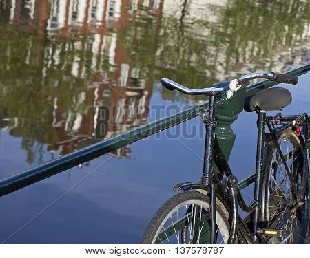 closeup of a bicycle near a canal reflecting houses in amsterdam