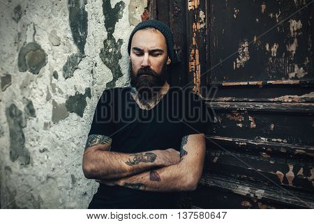 Portrait of brutal bearded man wearing blank t-shirt on the dor
