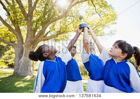 close up view of children soccer team arms in the air with cup in park
