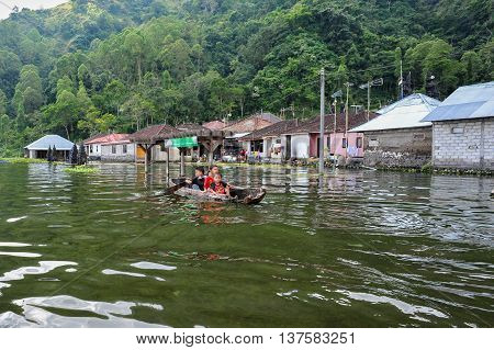 BALI, INDONESIA, 26 MAY, 2015: Children swimming with a wooden boat in Trunyan Village of Bali Indonesia