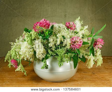 Alfalfa meadowsweet. Still life. Bouquet of meadow flowers in white pots standing on a wooden table. Rustic style.