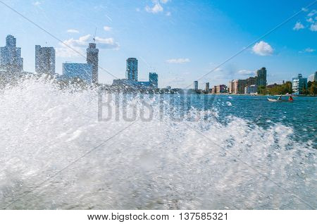 YEKATERINBURG RUSSIA - AUGUST 24 2013. Urban water landscape - modern business and administrative skyscraper buildings on the embankment of Iset river with splashing water on the foreground