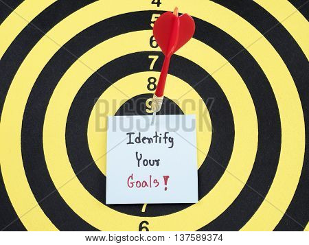 Handwriting Identify your goal on notepaper with dart arrow and dart board.