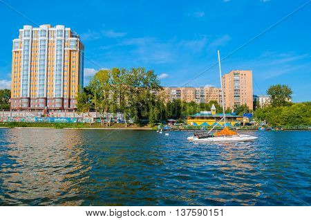 YEKATERINBURG RUSSIA - AUGUST 24 2013. Urban architecture view of modern residential buildings on the embankment of Iset river in Yekaterinburg in summer sunny day and sailboat on the foreground
