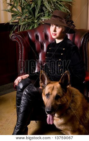 young woman sitting on a leather armchair and stroking the dog poster