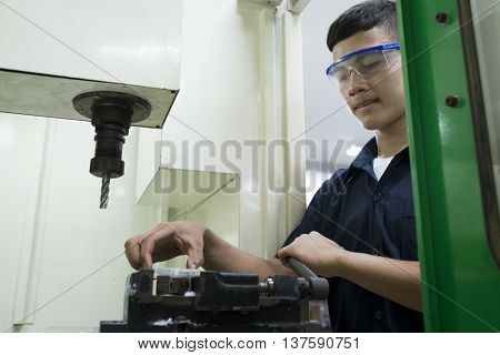 Technician controlling CNC machine.Man input workpiece to machine.