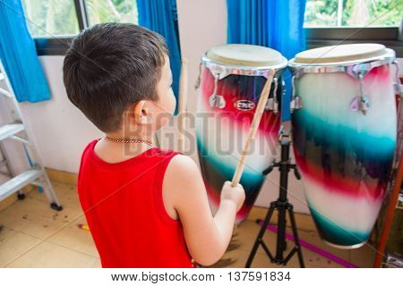 A boy holding a drumstick in the music room.Beginners
