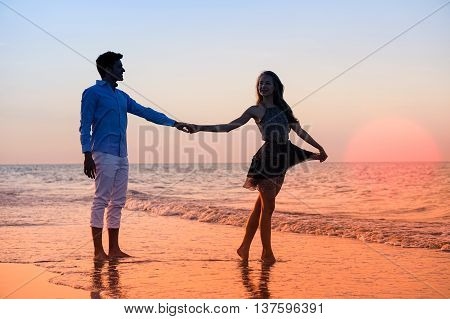 Silhouette of young couple walking at sunset on the beach - Happy lovers holding hands at night by the ocean with big red sun background - Iconic concept of love and tropical holidays with warm colors
