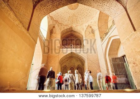 ISFAHAN, IRAN - OCT 17, 2014: Many tourists watching ancient interiors of the palace Ali Qapu with brick arches on October 18, 2014. Safavid era palace Ali Qapu was built in early 17th century in Esfahan