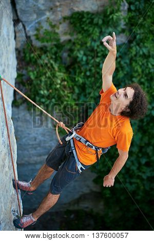 male rock climber. rock climber climbs on a rocky wall. man hanging on a rope and shows his hand up