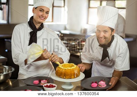 Portrait of two chefs preparing a cake in commercial kitchen