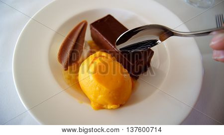 Gateau of dark chocolate with compote of exotic fruits and mango passion fruit sorbet