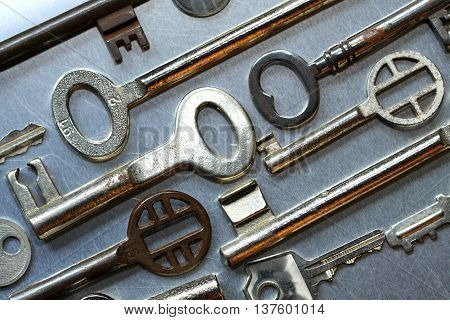 Small and large old house keys against metal background