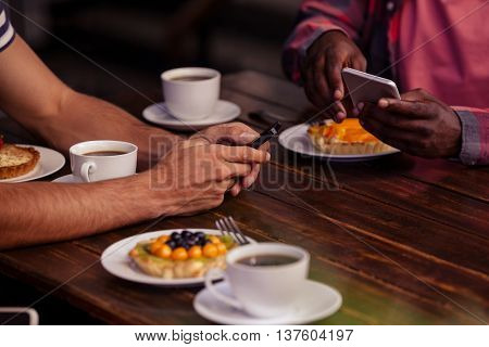 Cropped image of friends eating pastries and drinking coffee at coffee shop