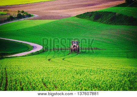 Farm machinery spraying insecticide to the green field, agricultural natural seasonal spring background, vintag retro hipster style