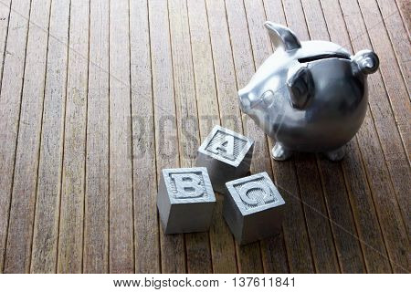 Piggy  Bank and Alphabet Cubes on Wooden Background