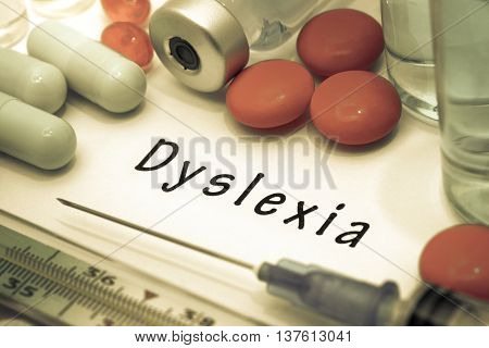 Dyslexia - diagnosis written on a white piece of paper. Syringe and vaccine with drugs.