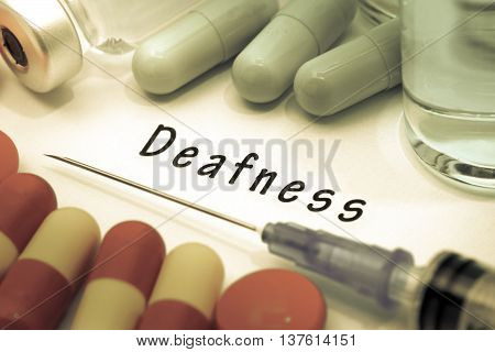 Deafness - diagnosis written on a white piece of paper. Syringe and vaccine with drugs.