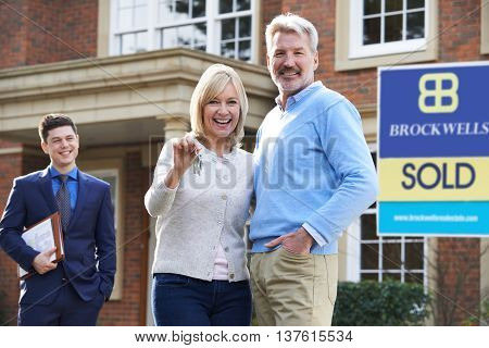 Mature Couple Collecting Keys To New Home From Realtor