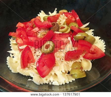 Pasta Salad with bow tie pasta, tomatoes, olives and parmesan cheese.