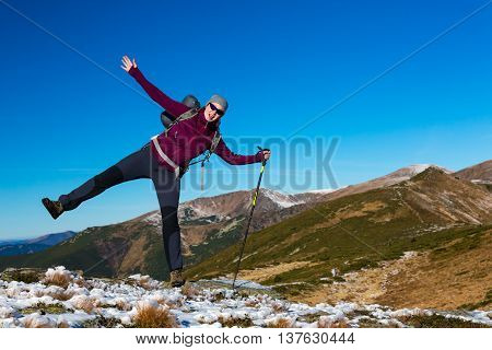 Female Hiker staying unstable on one leg falling on side in Mountains View with Autumnal Colors and blue Sky background