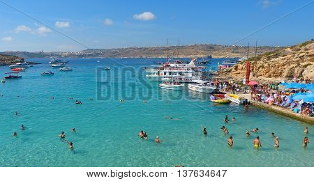 Comino, Malta - September 28, 2013. View of the Blue Lagoon on Comino island of Malta, with people, cruise boats and Gozo island in the background. The incredibly beautiful and inviting Blue Lagoon is the biggest attraction of Comino. It is a sheltered co