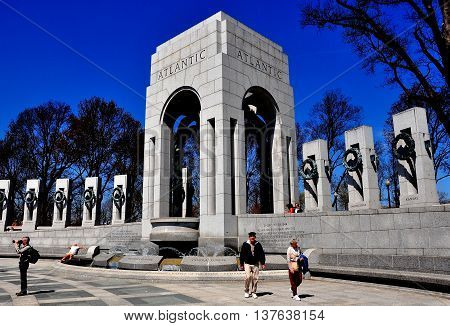 Washington DC - April 10 2014: Visitors at the moving World War II Memorial on the National Mall with the Atlantic Pavilion and States steles *