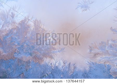 Fantastic abstract winter background (frost pattern on a window glass at the dawn) winter morning