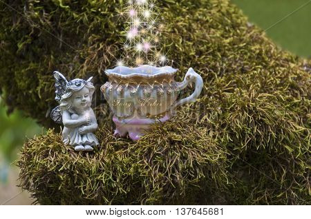 Small fairy sitting on mossy branch next to a magical fairy teacup. There are whimsical sparkles of light flowing into the teacup.