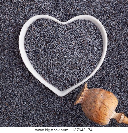 Poppy seed background. Poppy seeds in heart shaped bowl top view. Healthy eating.
