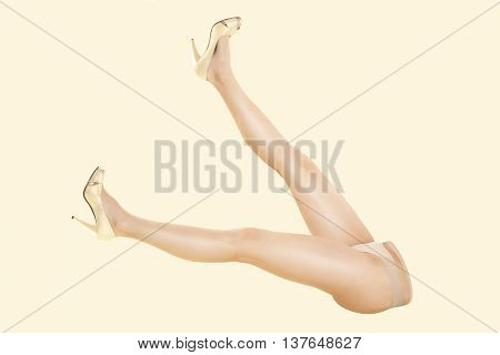 Sexy female legs with golden high heels isolated on beige background. Sexy provocative seductive. Fashion doll concept.