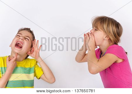 Deaf child - Boy cupping his hand behind ear because he cant hear the girl who is shouting in vain