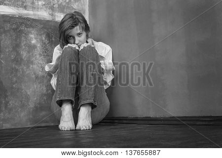 Alarmed woman sitting on the floor in the corner of a grungy room. Resentment anxiety or social phobia concept